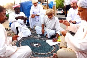Merchants in an Al-Buraimi, Oman market take a card-game break